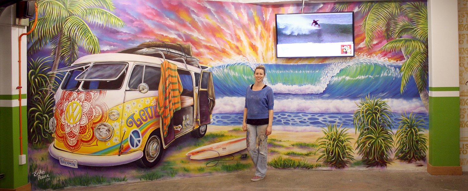 Erika in front of a mural she painted with a combie van, surf breaking at the beach