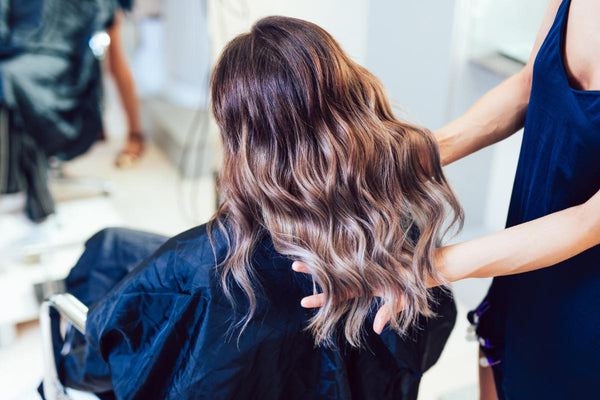 Young woman getting beautiful hairstyle in hair salon.