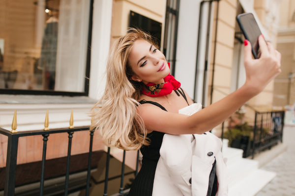 Beautiful woman smiling and taking a selfie outside.