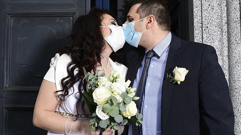 Bride and groom kissing in face masks