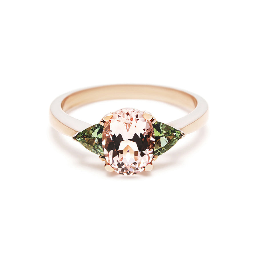 The Tavi engagement ring looks beautiful on the finger with it's tapered band and oval morganite. Locally cut green sapphires give the illusion of leaves on a flower. This is a feminine and elegant ring for a bride looking for an diamond alternative.