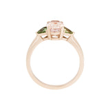 This is a side view of the Tavi ring, which features an oval morganite and hand-cut green sapphires. The ring is made in a 14 karat rose gold setting which adds warmth and compliments the pink morganite.