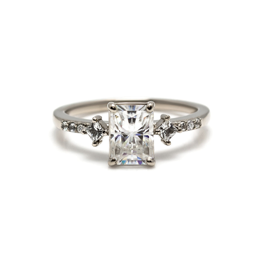 The May ring is a modern engagement ring or right hand ring that features an emerald cut center diamond with kite set side diamonds and a pavé diamond band. Made in 14 karat white gold, yellow gold or rose gold. Pairs well with a diamond wedding band.