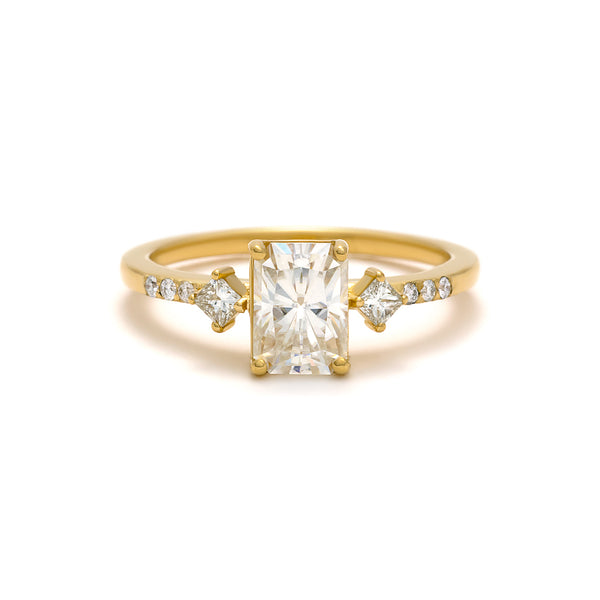 The May Ring features an emerald cut diamond with kite-set princess cut side diamonds. Made of 14 karat yellow gold.