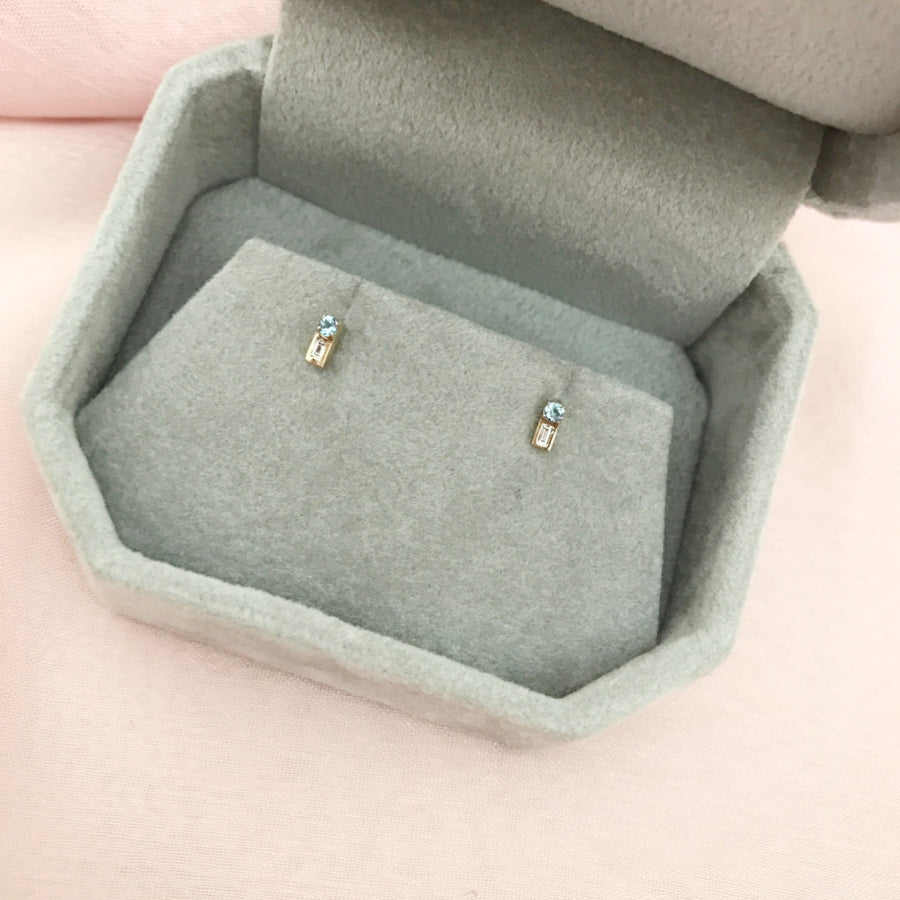 The Renata Earring is a small 14 karat yellow gold stud set with a small round London Blue topaz gemstone and a baguette diamond.