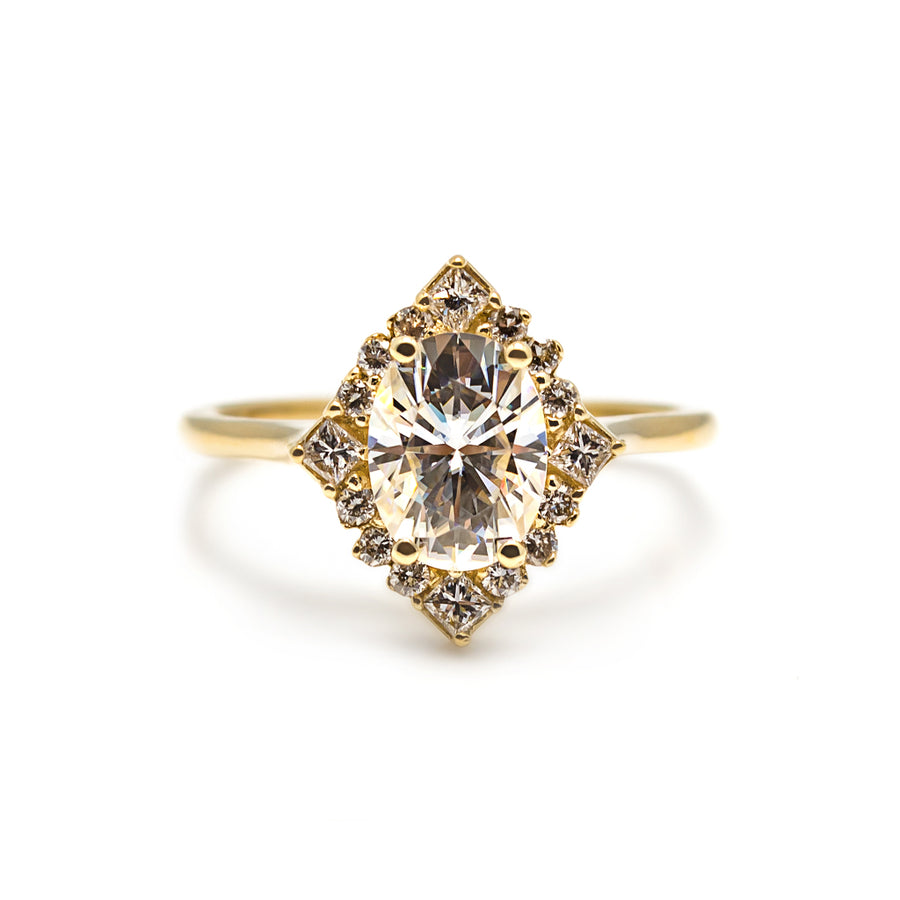The Caroline Ring: featuring an oval moissanite center stone, a halo of round and princess cut diamonds and made in 14 karat yellow, rose or white gold.