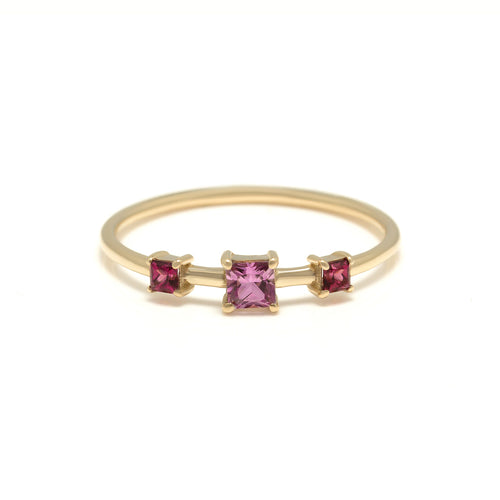 The Sloane Ring is a vibrant gemstone ring featuring a princess cut pink sapphire and two rhodolite garnets all set in 14 karat yellow gold.