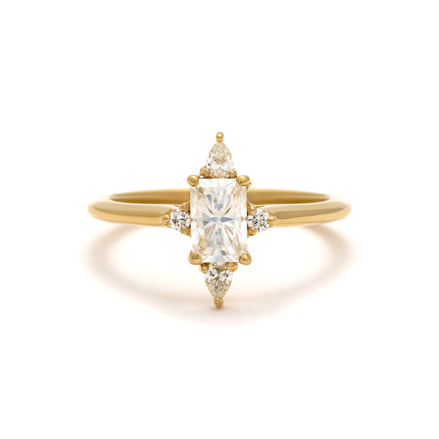 The Felicity Ring features a half carat emerald cut diamond with pear and round accent stones.