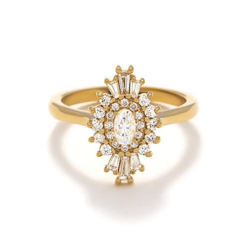 The Zina Ring is an Art Deco inspired engagement ring that features an oval center diamond flanked by round and tapered baguette diamonds.