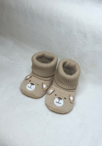 Beige knitted baby booties with bear face design on front of boot.