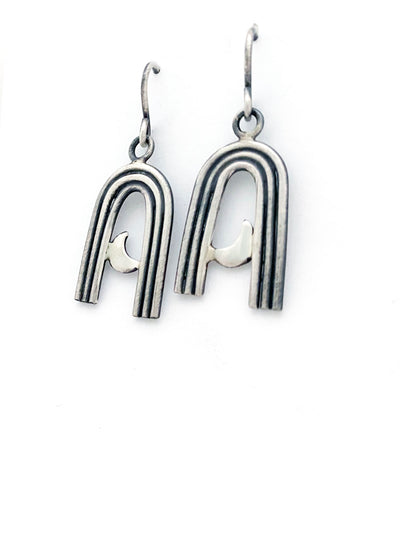 small silver rainbow shapes with crescent moons inside the arch. Dangle earrings with hook.