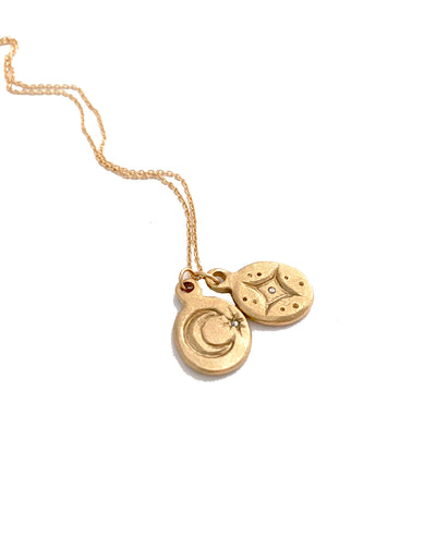 two small 14k gold charms on gold chain. One with a crescent moon, one with stars and diamonds