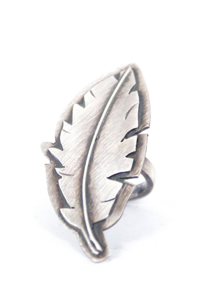 Feather Ring Front View, Feather ring Front View, cutout of an oxidized silver feather on a backplate
