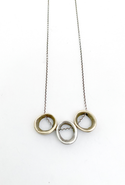 Loop Necklace Front View. Thin silver chain with three imperfect loop charms on it. Two are brass, one is silver