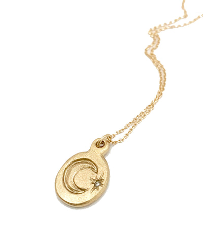 small oval 14k gold charm on gold chain. Charm has a carved crescent moon with a carved star and diamond next to it.