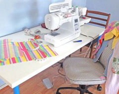 A shot of a sewing table with a multicoloured fabric project. There are sewing machines and tools on the table. There are chairs around the table.