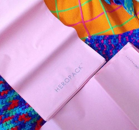 A close up of two pink compostable Hero Pack mailers with an orange and blue knit jumper in the background about to be packaged.