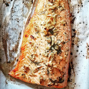 A big piece of salmon fillet covered in fresh garden herbs and roasted garlic