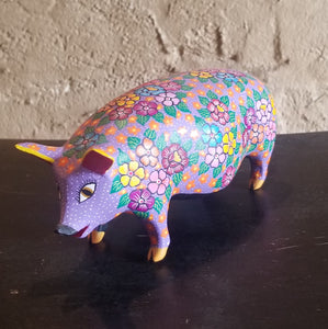 Carved pig with colorful flowers