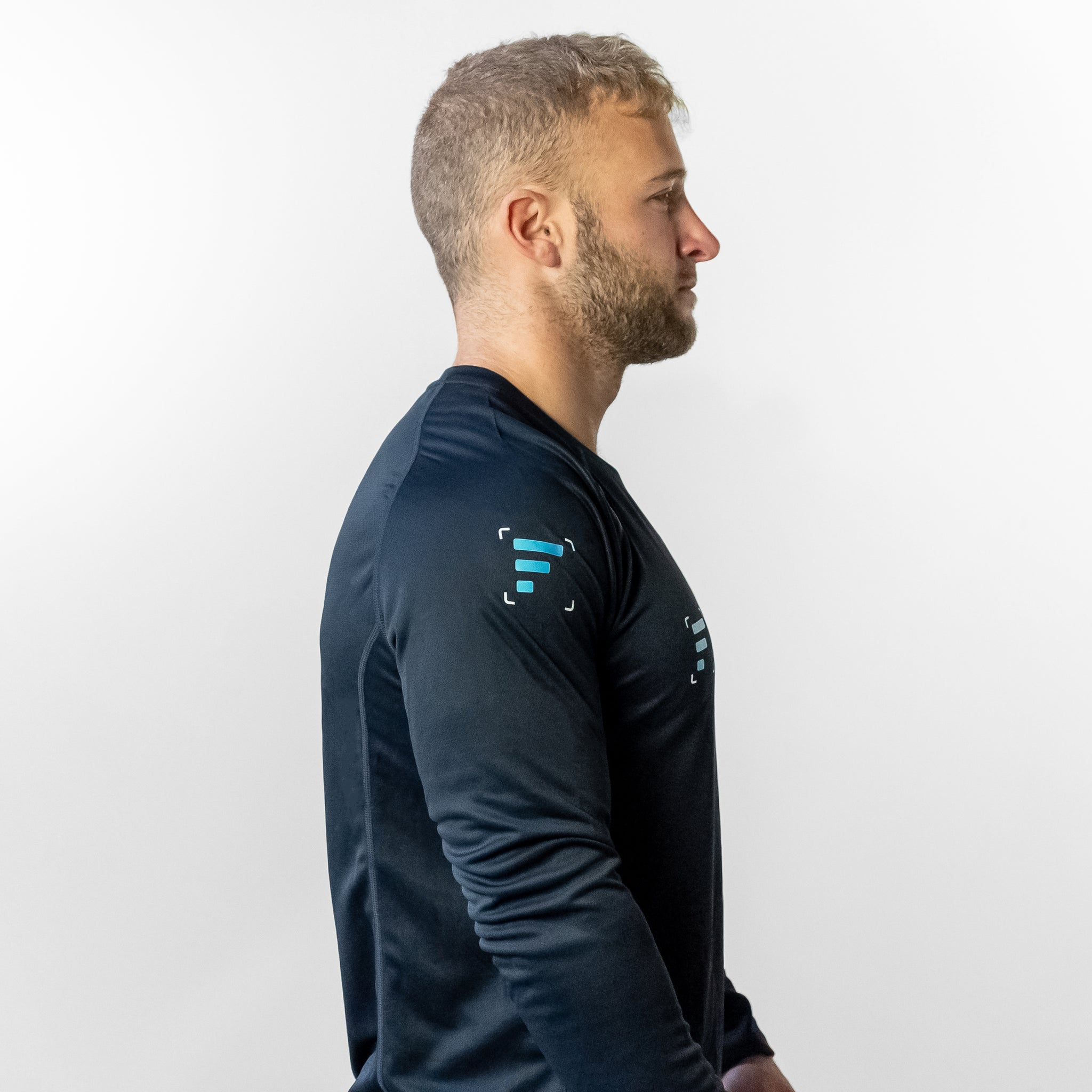 Side angle of man wearing FlexIt Dry Fit black long sleeve shirt.