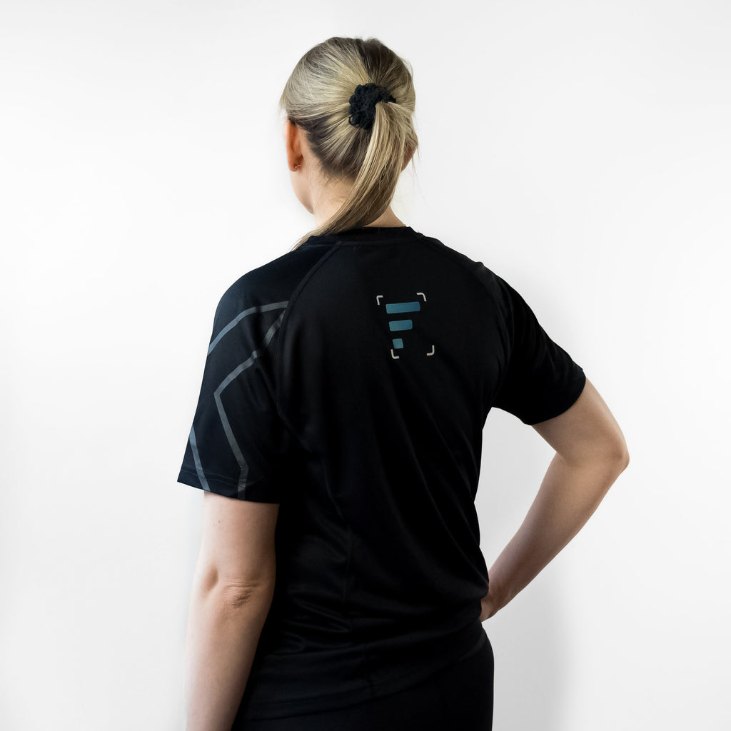 Back angle of woman wearing FlexIt Dry Fit black t-shirt.