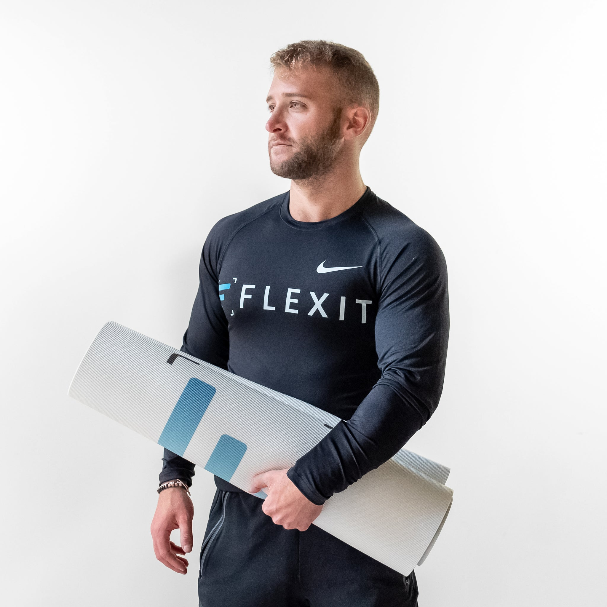 Man holding FlexIt yoga mat in hand.