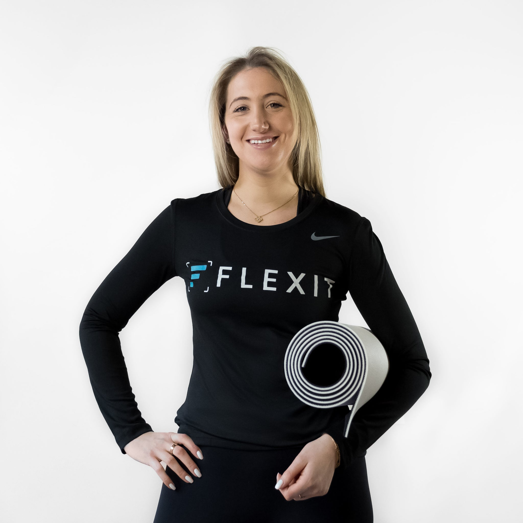 Woman holding FlexIt yoga mat in hand.