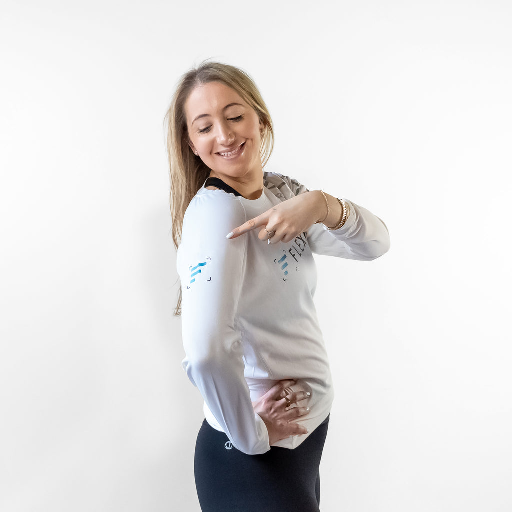 Woman pointing to FlexIt logo on the side of the Women's Dry Fit Long Sleeve shirt.