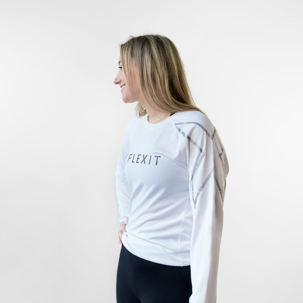 Side angle of woman wearing FlexIt Dry Fit white long sleeve shirt.