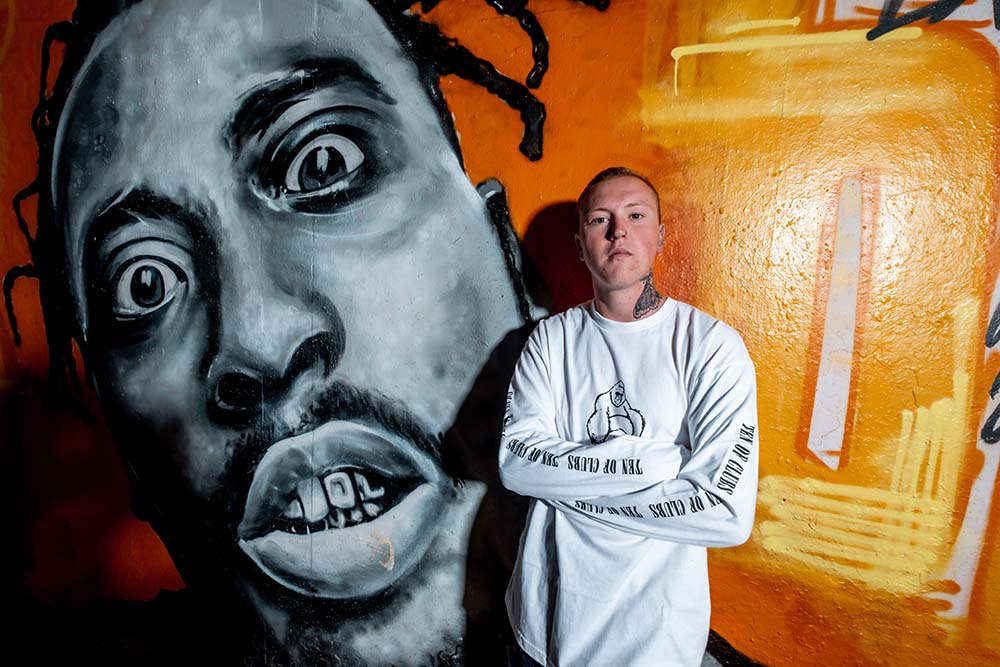 Man in Kong Long Sleeve t-shirt from Ten of Clubs stood in front of painted wall mural