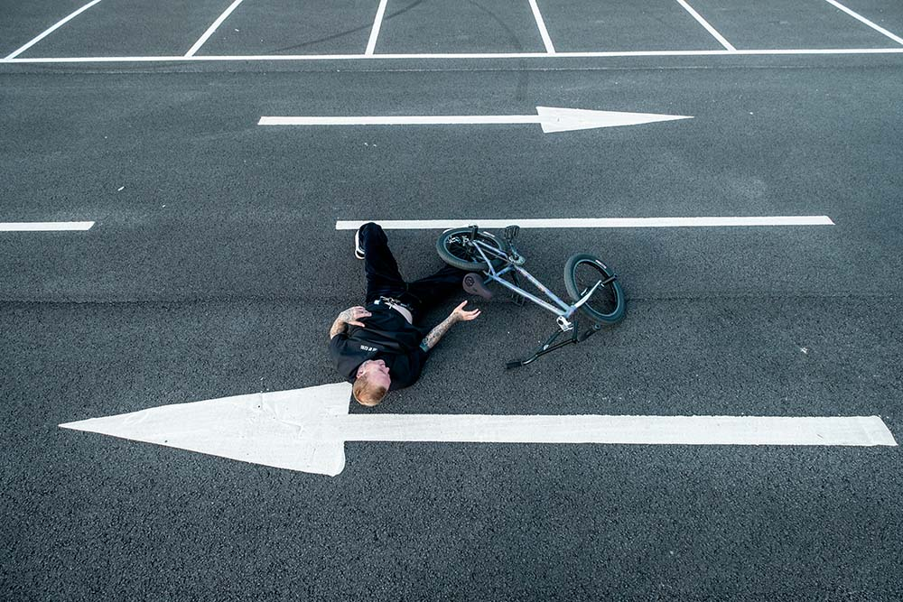 Man in Wave Tee from Ten of Clubs lay on the ground next to crashed BMX
