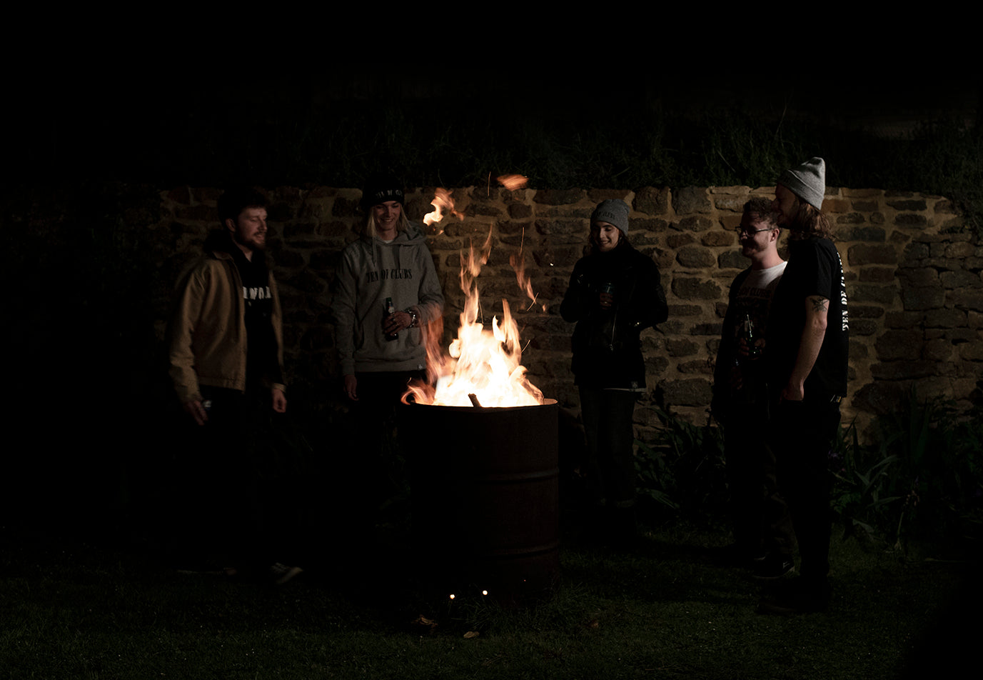 Group of young people in apparel from Ten of Clubs gathered around a burning brazier