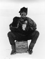 Steward Hooper eating baked beans on a wooden box advertising Heinz