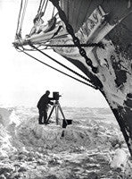 Frank Hurley with movie camera beneath the bow of the Endurance
