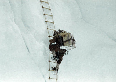 A Sherpa carrying gear on a rope ladder in the icefall