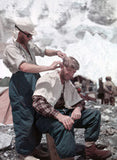 Charles Evans cutting George Lowe's hair at Base Camp