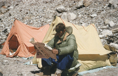 Edmund Hillary reading a newspaper (New Zealand Illustrated) at Camp I