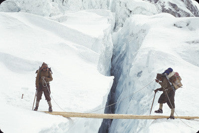 Sherpas wearing crampons crossing log bridge