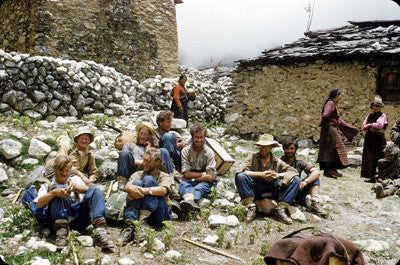 Team members resting on rocks in a Nepali village