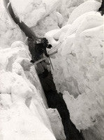 A Sherpa crossing a crevasse on a ladder between Camps II and III