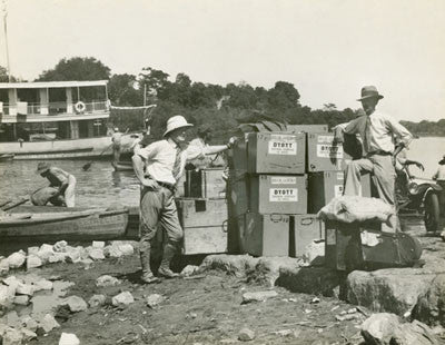Expedition members with boxes on the river side