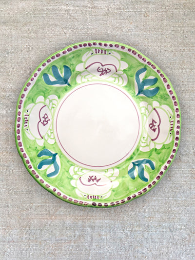 A hand painting dinner plate in green and purple. Painted on the plate is four frogs.