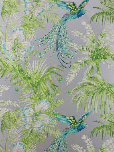 Blue birds of paradise flying through the trees in a jungle. The wallpaper has a silver ground.