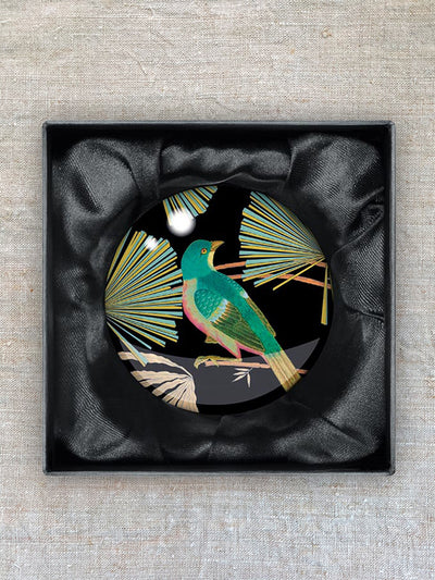 A glass paperweight showing a green bird perched on bamboo.
