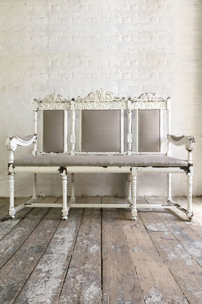 A painted white carved wood hall bench. With flaking paint and grey fabric upholstery.