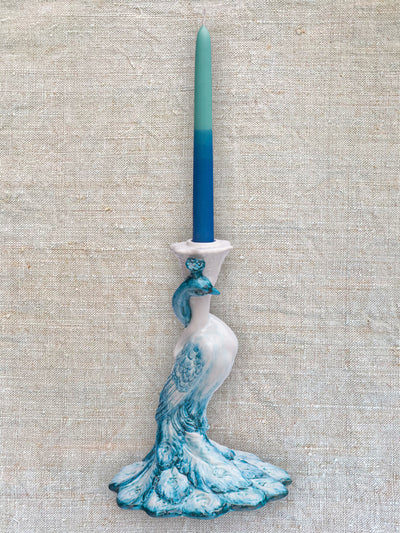 A ceramic peacock candlestick with blue feathers. The candlestick holds a single two tone blue candle.