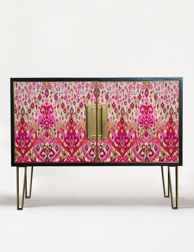 A sideboard upholstered in sumptuous silk-blend fabric and beautifully accented with brass door frames, handles and legs. Ikat Animal in pink is an abstract print created exclusively for the collection