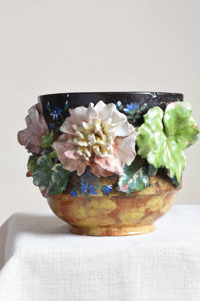 An antique majolica plant pot. Vine leaves and peonies adorn the circumference of the vessel, offset by hand-painted, electric blue agapanthuses.