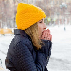 Winter Acne, young woman warming her hands in the cold