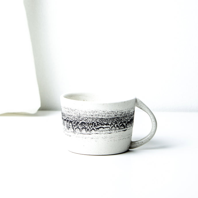 -Latte / Cappuccino Coffee Cup -Clear glaze on white porcelain clay -Slight angle toward lip, low and wide opening with lip to bottom full arch handle -Modern simple shape + natural texture *BasaltCollection Drawing of mixture of dark minerals. The unique organic drawing is applied in a rotation motion of my wheel.